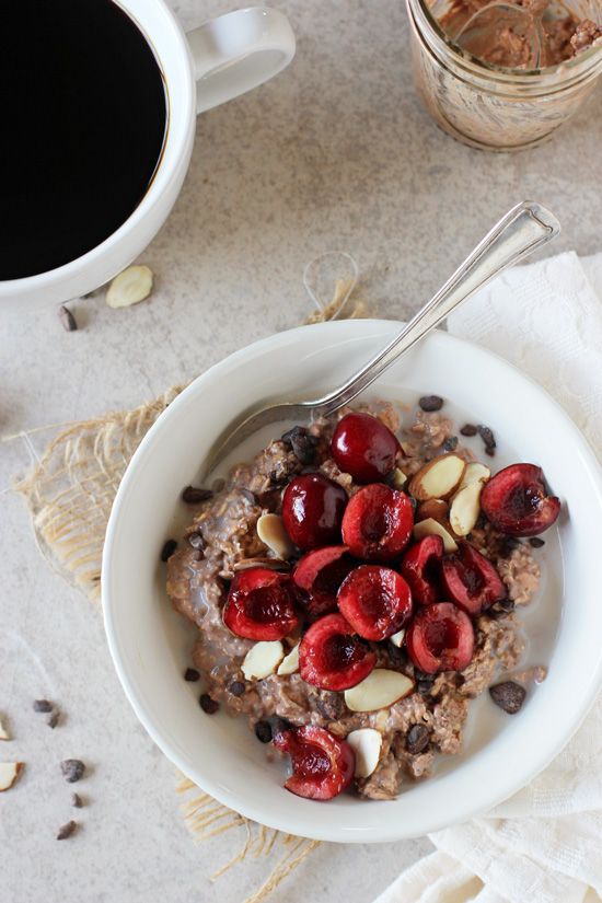 A white bowl filled with Cherry Overnight Oats with a cup of coffee to the side.
