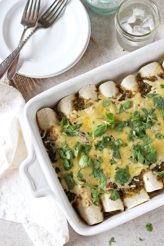 Recipe for fresh corn, zucchini and black bean enchiladas. With a creamy filling from a sauce made of fresh corn kernels! Topped with salsa verde and cheese!