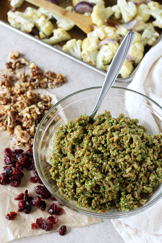 A glass mixing bowl filled with Pesto Farro and a tray of roasted cauliflower in the background.