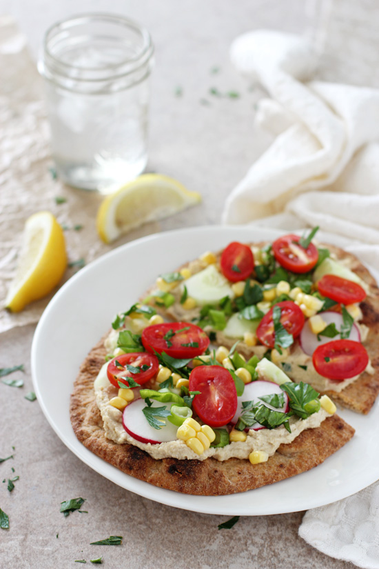 A white plate with a Summer Garden Veggie Flatbread with water and lemon to the side.