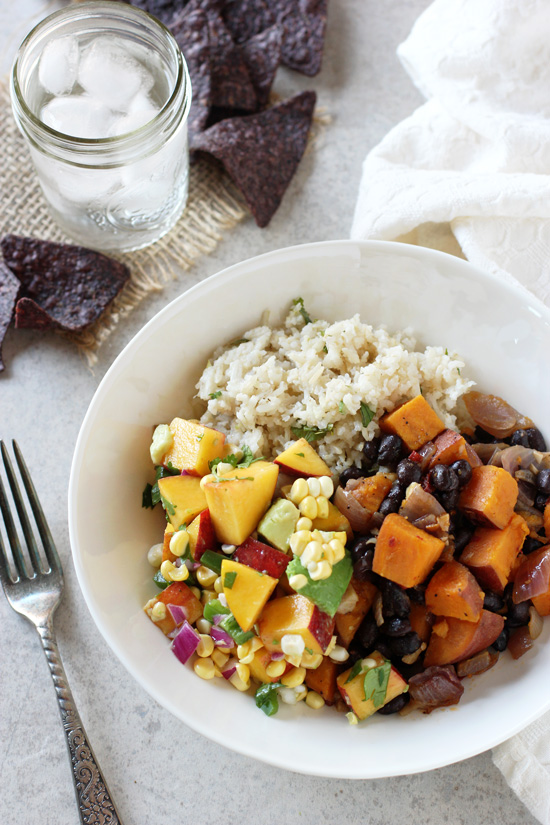 A white dish filled with Chipotle Sweet Potato Burrito Bowls with a fork to the side.