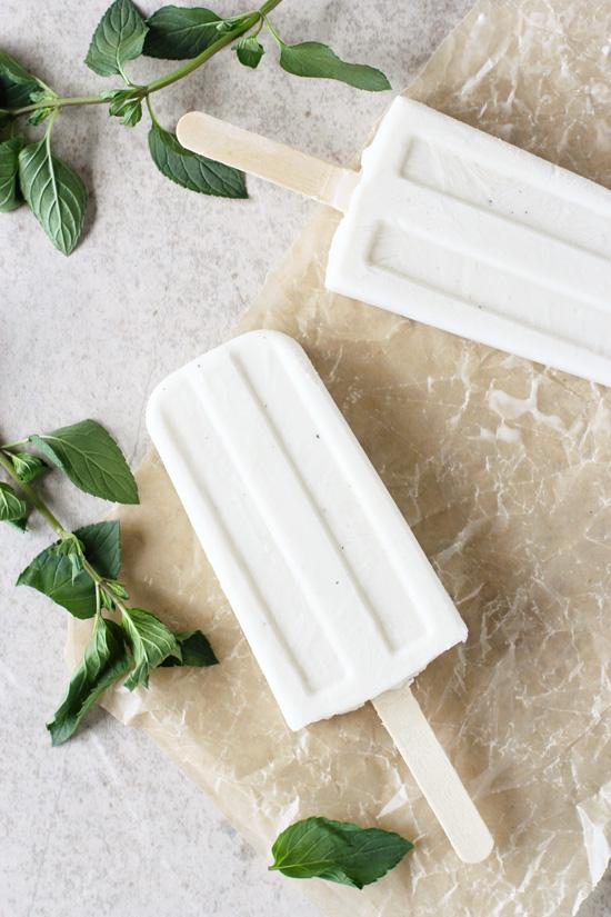 Two Creamy Coconut Mojito Ice Pops on parchment paper.