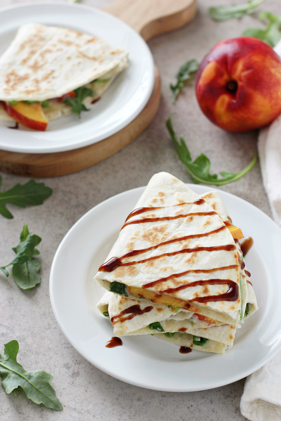 Several triangles of Peach and White Bean Quesadillas on white plates.