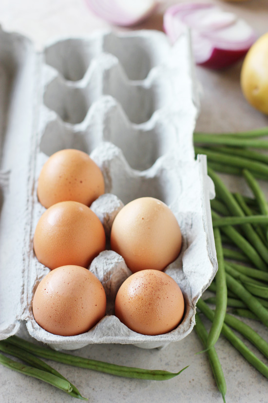 An opened egg carton and fresh green beans to the side.