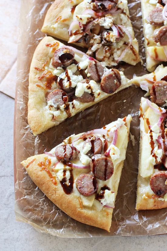 A sliced Apple Bratwurst Pizza on a wood cutting board.
