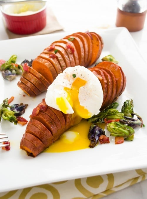 A white plate with two Hasselback Sweet Potatoes.