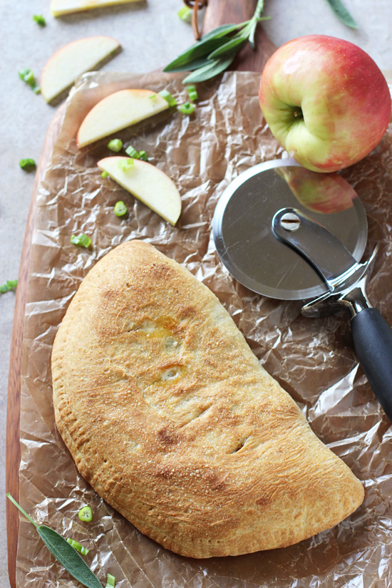 An Apple Cheddar Calzone on a wood cutting board with a pizza cutter.