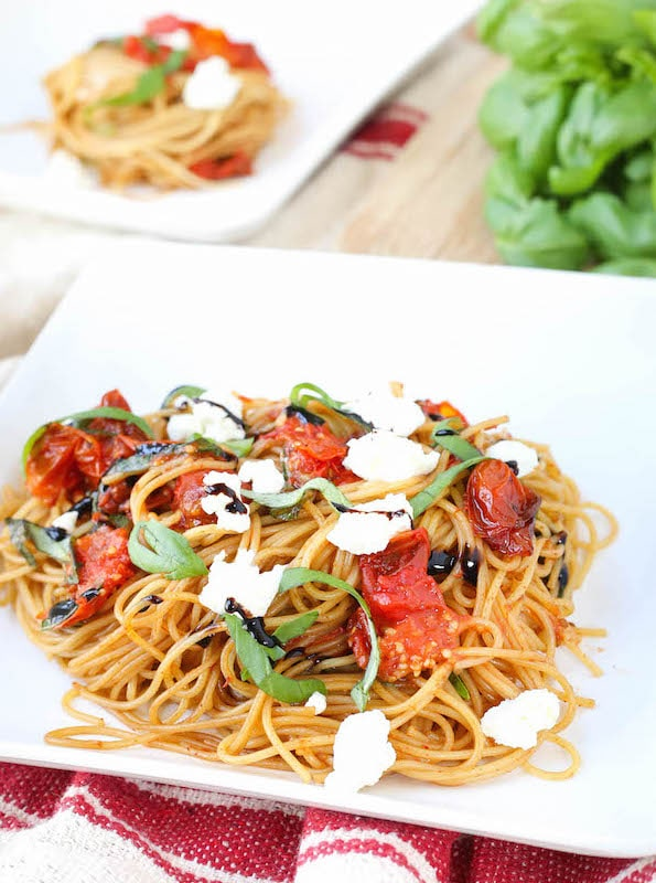 A white plate filled with Roasted Tomato Basil and Goat Cheese Pasta.
