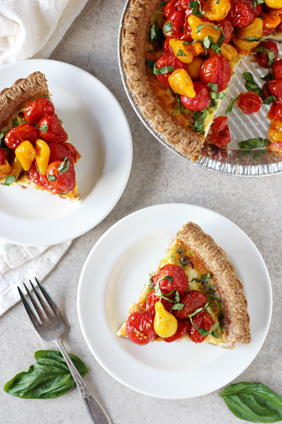 Two slices of Tomato and Goat Cheese Quiche on white plates.