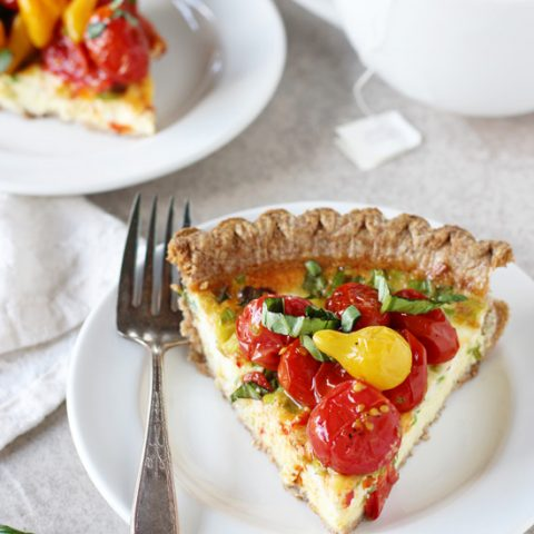 Recipe for tomato and goat cheese quiche. A simple, make ahead dish filled with green onions and goat cheese! And topped with plenty of roasted tomatoes!