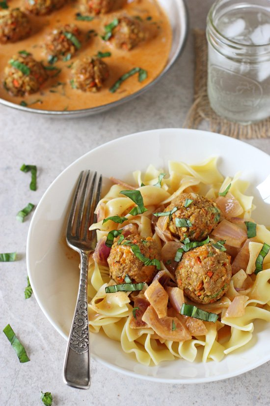 Recipe for thai red curry baked vegetable meatballs. Flavorful veggie and chickpea meatballs served in a creamy thai red curry sauce! Finished with fresh basil!