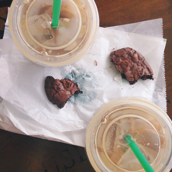 Two iced coffees and a chocolate cookie split in half.