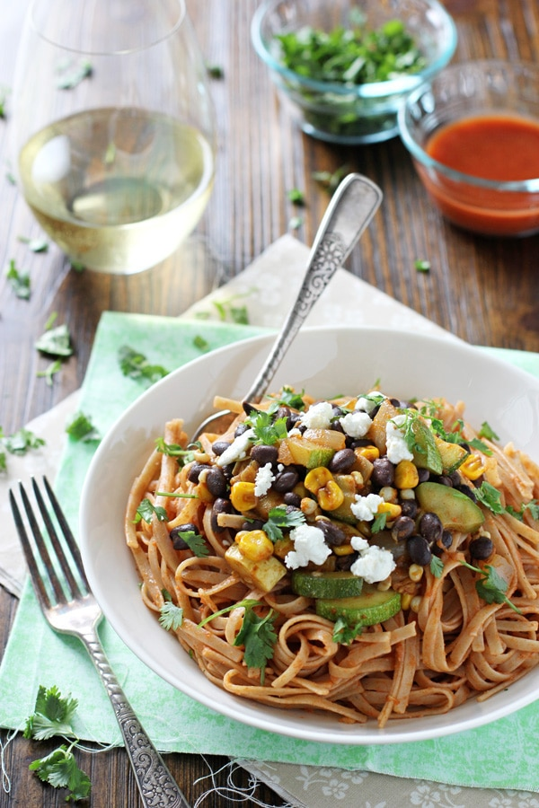 A white bowl filled with Vegetable and Black Bean Enchilada Pasta.