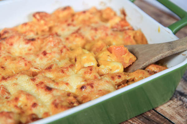 A green baking dish filled with Baked Butternut Squash and Gouda Tortellini.
