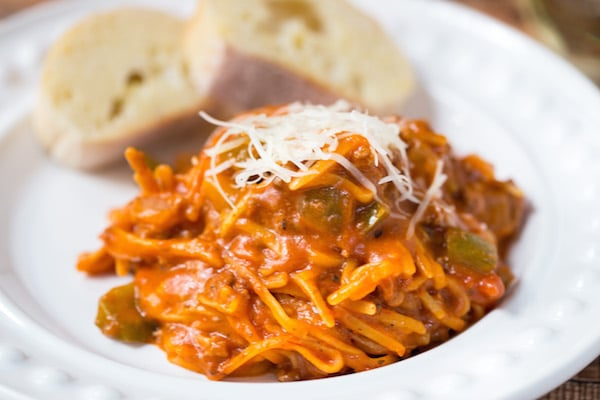 A white plate filled with One Pot Weeknight Spaghetti and bread.