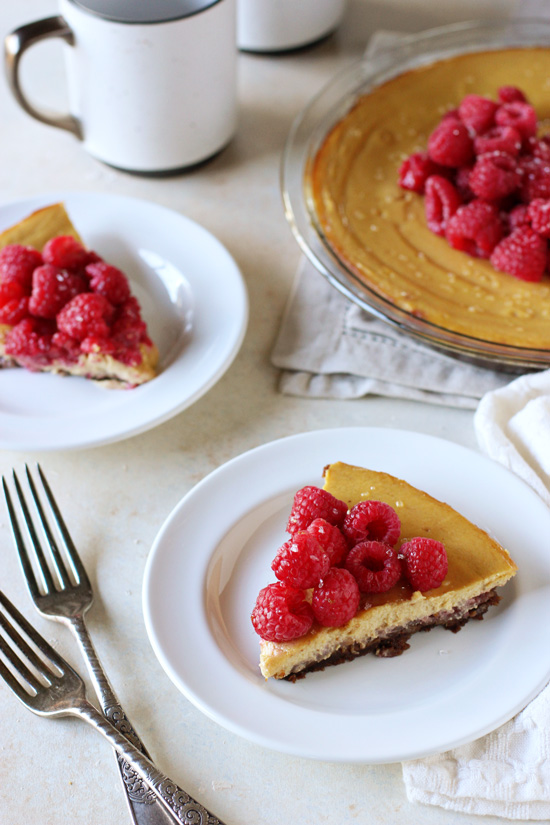 Two slices of Raspberry Pumpkin Ricotta Pie with the full pie in the background.