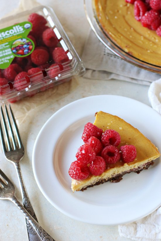 A slice of Pumpkin Raspberry Pie on a white plate.