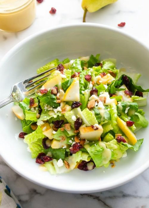 A white bowl filled with Cranberry Pear Salad with Fresh Pear Vinaigrette.