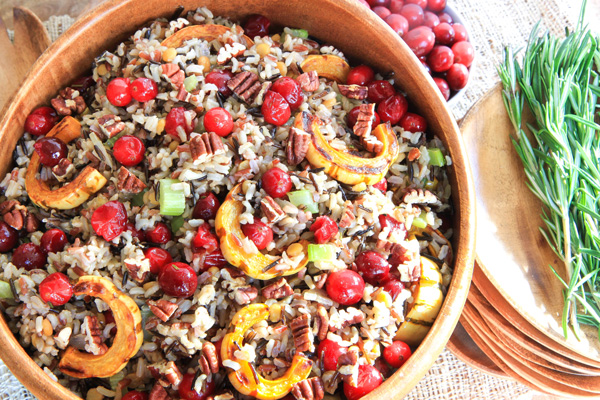 A wooden bowl filled with Cranberry and Squash Wild Rice Salad.