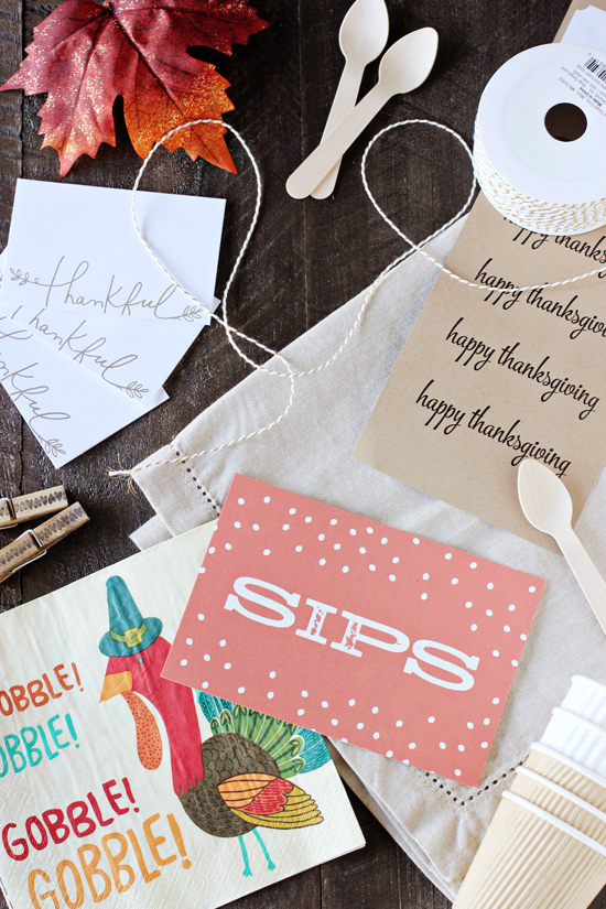 Assorted Thanksgiving napkins, place cards and decor on a wooden surface.