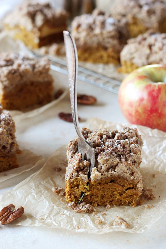 A slice of Pumpkin Apple Crumb Cake with a bite taken out with a fork.