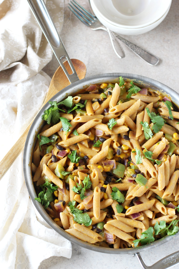 An all-clad skillet filled with Creamy Sweet Potato and Black Bean Pasta.