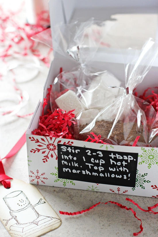 A Homemade Hot Chocolate Gift set on a white surface with ribbon scattered around.