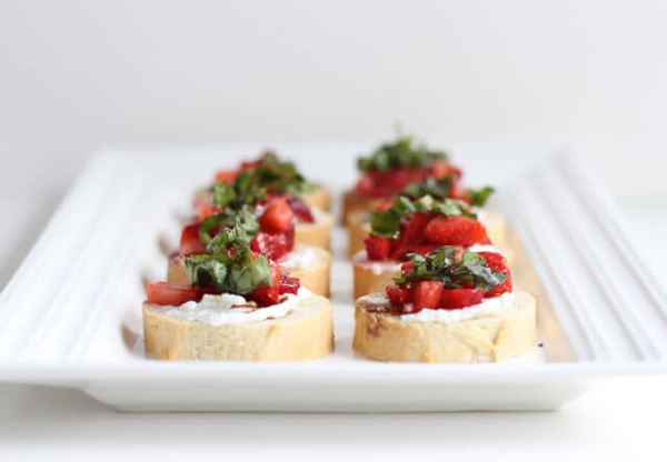 A white serving platter filled with Strawberry Bruschetta.
