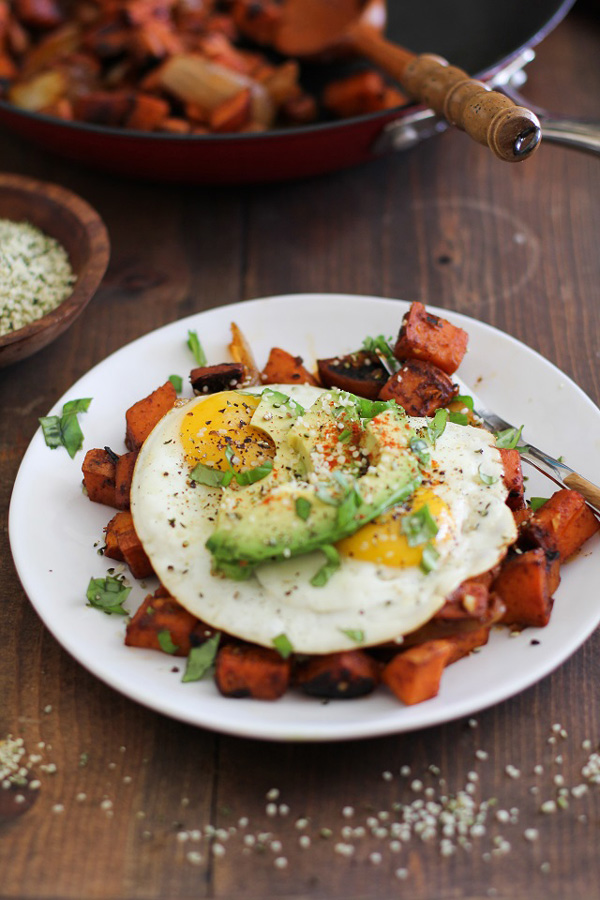 A white plate filled with Sweet Potato Home Fries and fried eggs.