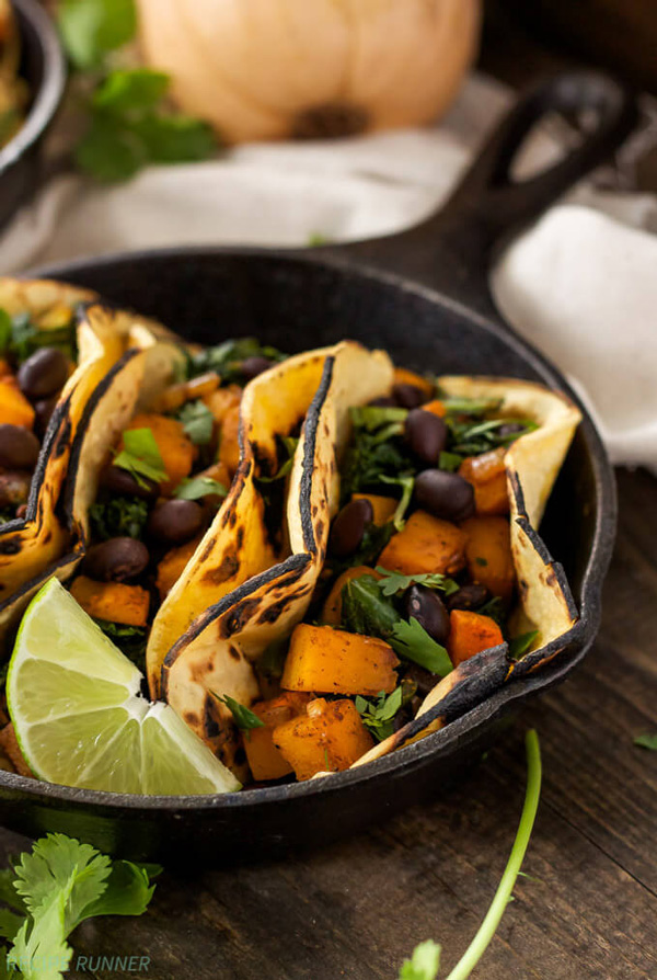 A black skillet filled with three Butternut Squash, Black Bean, and Kale Tacos.