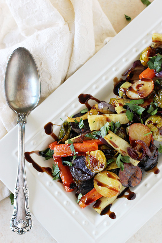 A white serving platter with Honey Balsamic Roasted Vegetables with a spoon to the side.