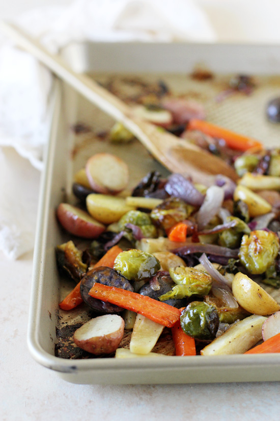 A baking sheet with Honey Balsamic Vegetables with a wooden spoon in the pan.