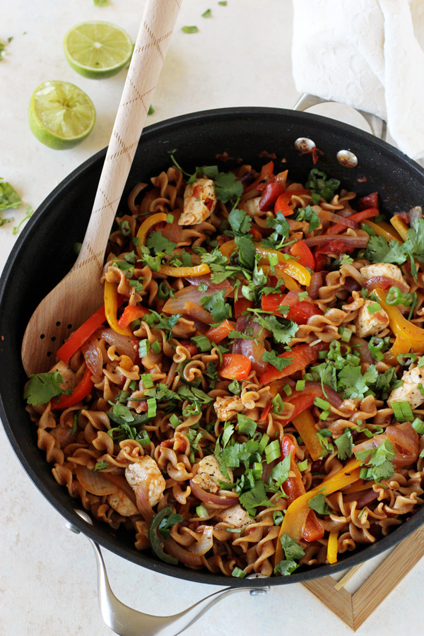 A black skillet filled with Chicken Fajita Whole Wheat Pasta.