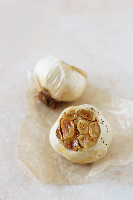 Two heads of roasted garlic on parchment paper.