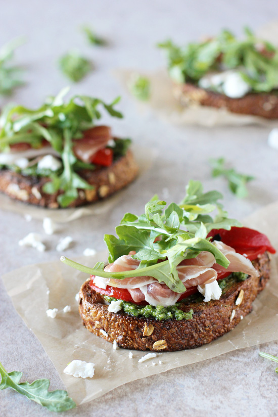 Three Arugula, Prosciutto and Goat Cheese Open Faced Sandwiches on parchment paper.