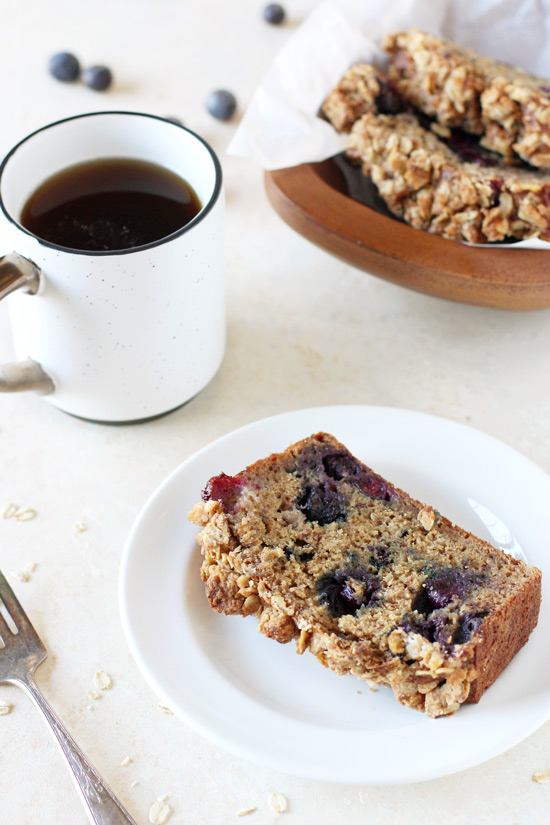 A slice of Blueberry Banana Bread on a white plate with coffee and more bread in the background.