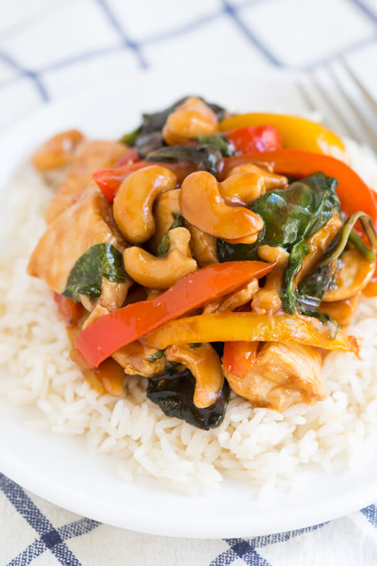 A white plate with Cashew Chicken with Peppers and Greens and rice.