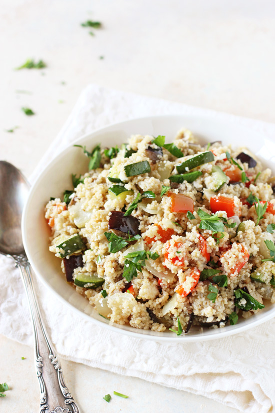 A white bowl filled with Mediterranean Couscous Salad with a silver spoon to the side.