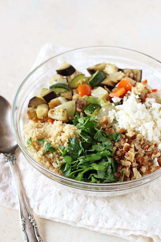 A glass bowl filled with couscous, roasted veggies, feta, walnuts and herbs.