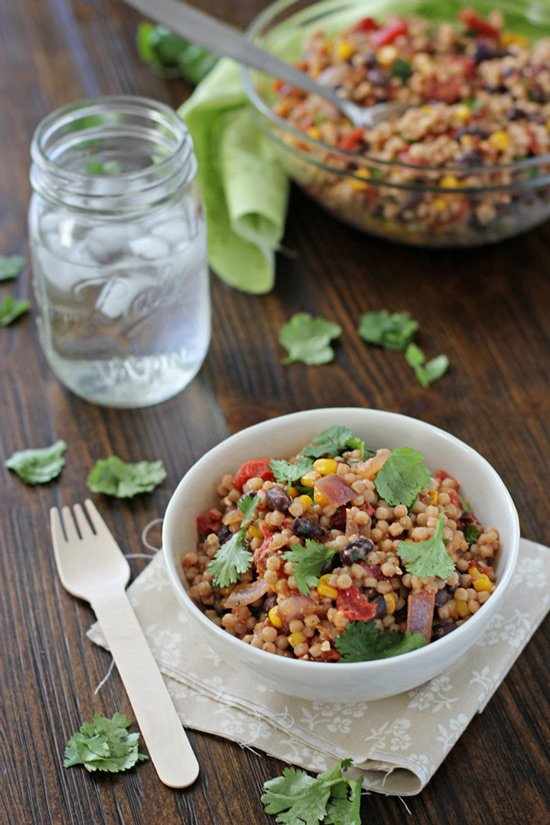 A white bowl filled with Mexican Couscous Salad with a serving dish in the background.