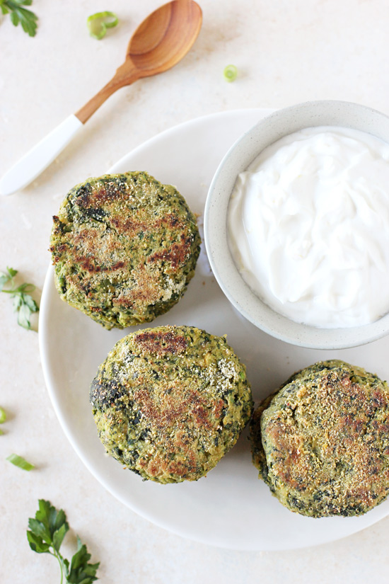 A white plate with three Spinach Falafel and a bowl of greek yogurt sauce.