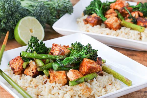 Two white plates with Sriracha Peanut Tofu Stir Fry and rice.