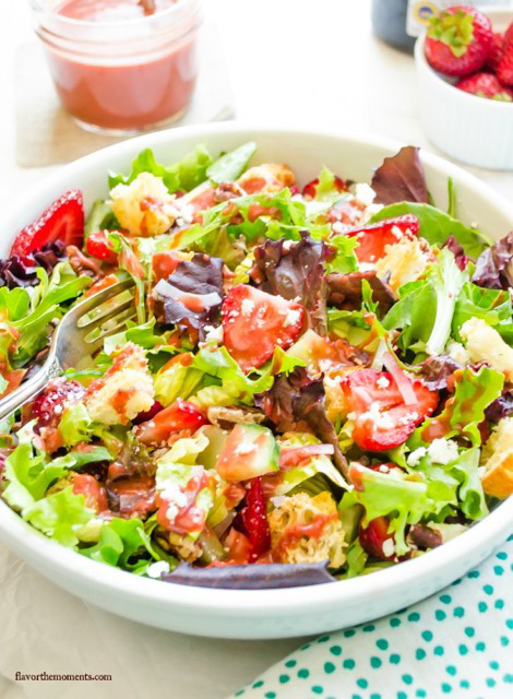 A white bowl filled with Strawberry Fields Panzanella Salad.