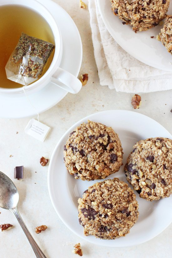 A white plate with three Banana Bread Breakfast Cookies with a cup of tea to the side.