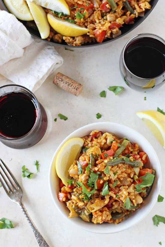 A white bowl filled with Vegetarian Paella with wine glasses and a skillet in the background.