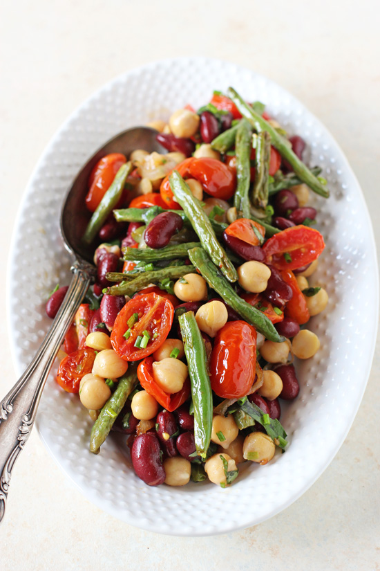 A white serving platter filled with Healthy Three Bean Salad with a silver serving spoon.