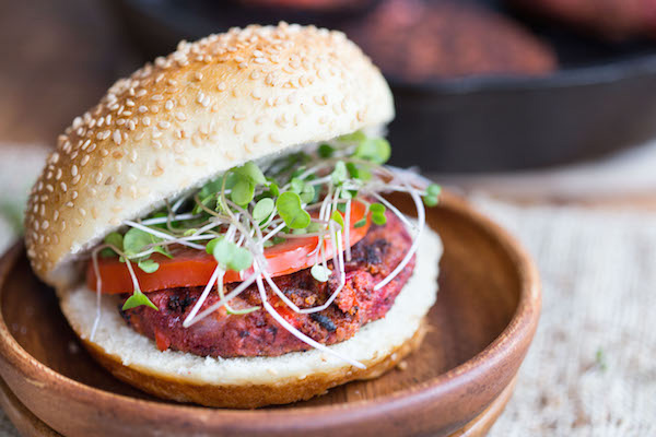 A Smoky Beet and Quinoa Veggie Burger on a wooden plate.