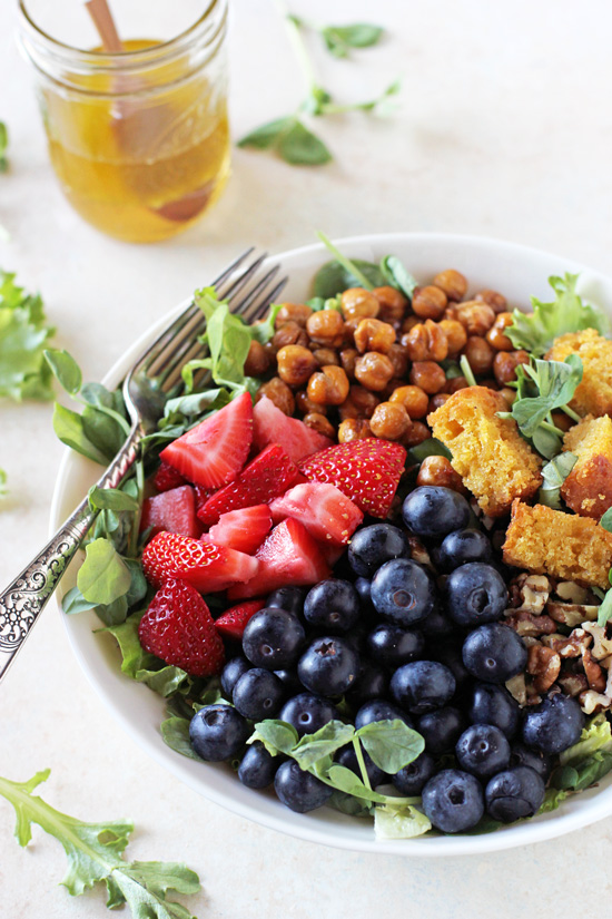A white bowl filled with Summer Berry Chopped Salad with a jar of dressing in the background.