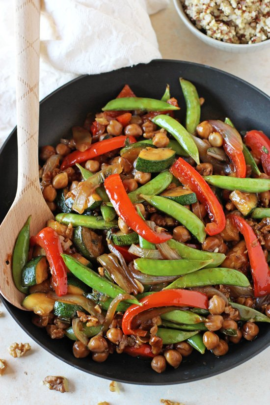 A black skillet filled with Bell Pepper, Snap Pea and Zucchini Stir-Fry with a wooden spoon in the pan.