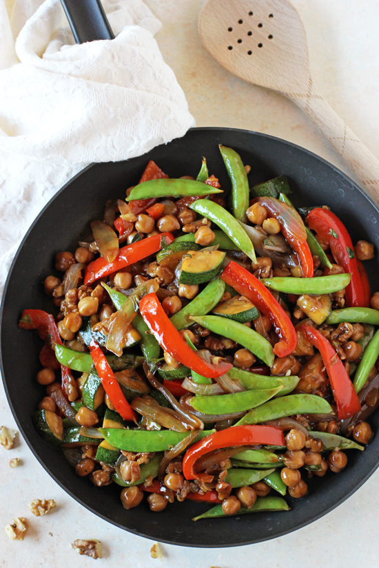 A black skillet filled with Bell Pepper Stir-Fry with a wooden spoon to the side.